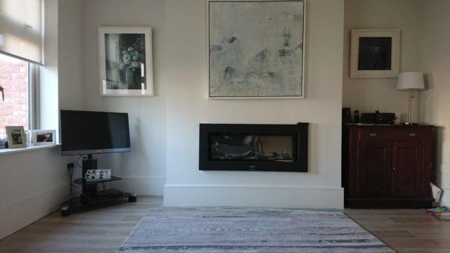 窓側に置かれたテレビと部屋の中心にある電気暖炉