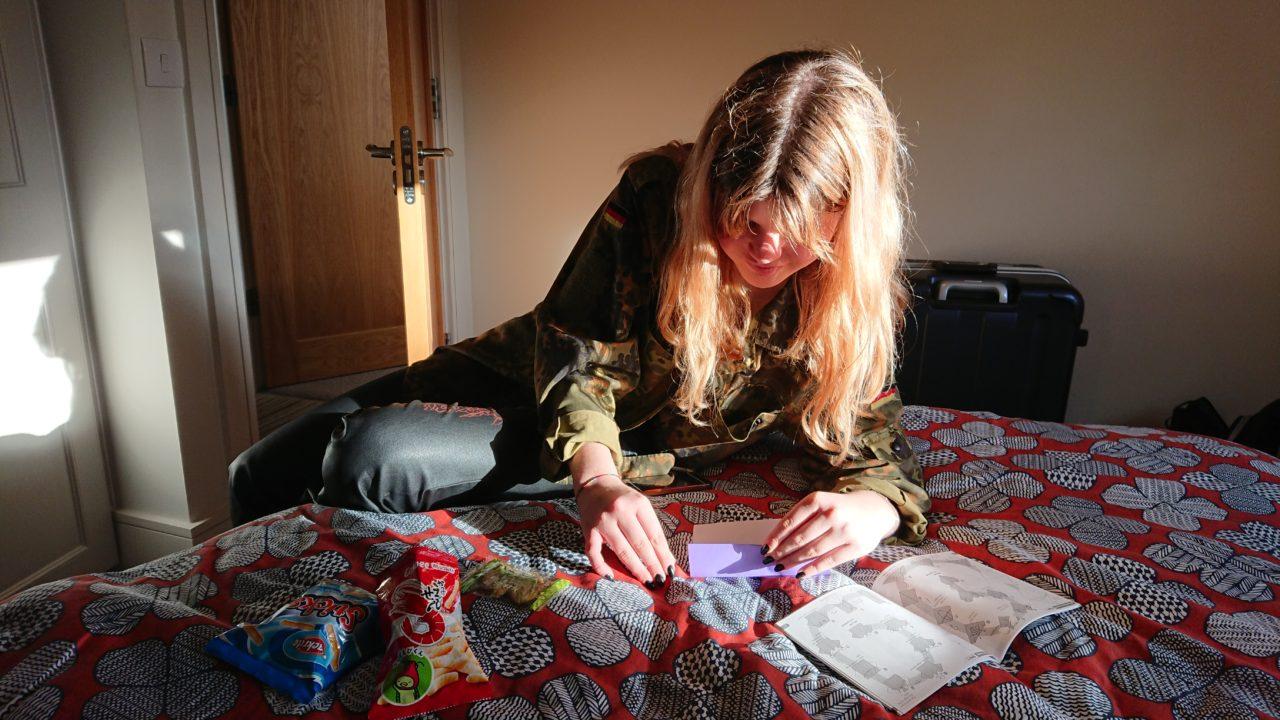 ベッドの上で折り紙をするイタリア人