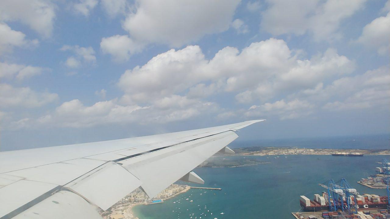 飛行機の窓から見下ろした街並みと海
